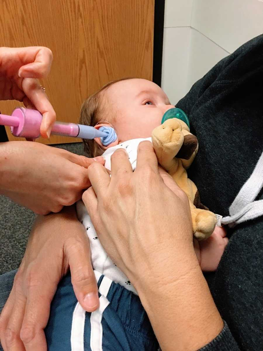 A little boy getting hearing aids at the doctor