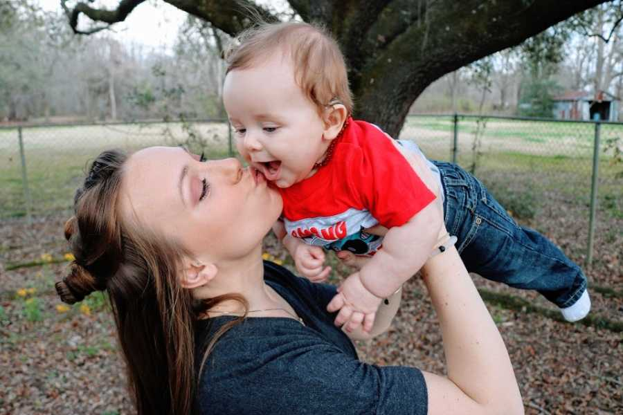 A mother holds her baby boy over her head and kisses him