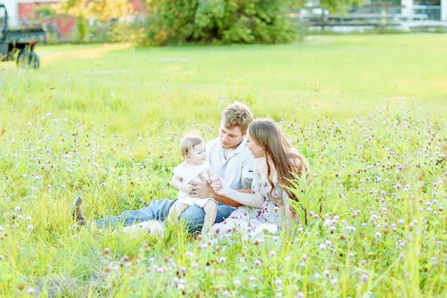 Parents sit in a field with their young son