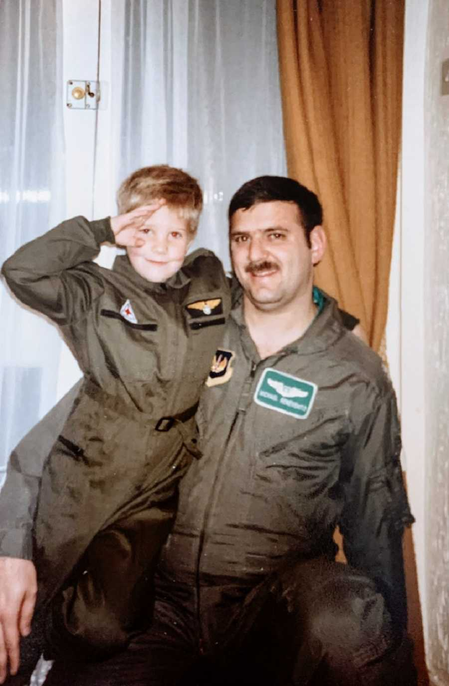 A man in a military uniform stands with a young boy
