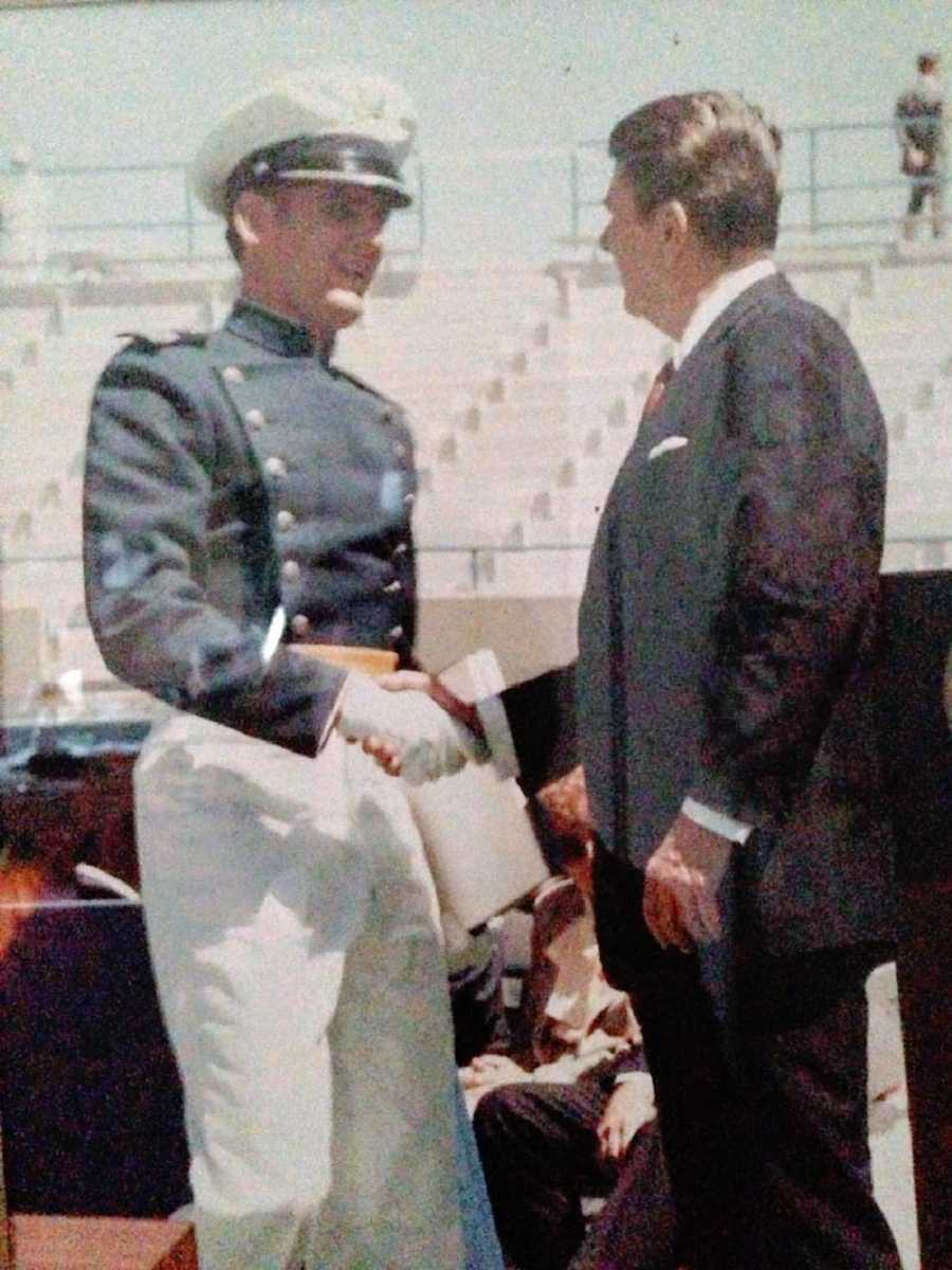 A young man in a military uniform shakes another man's hand