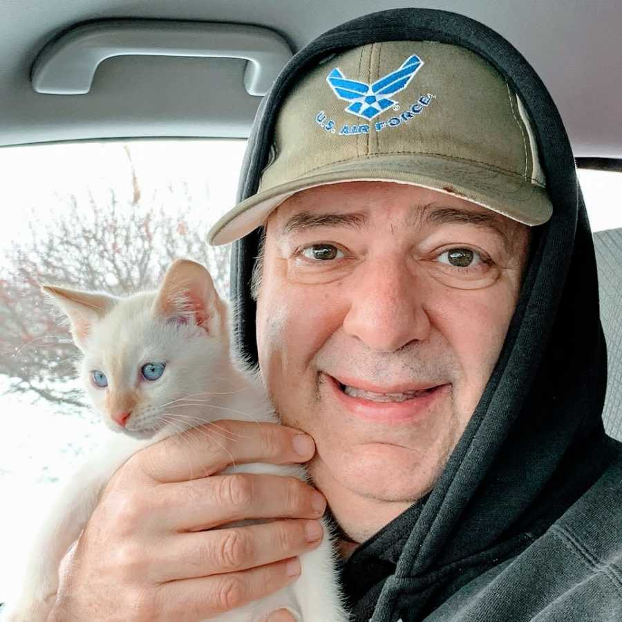 A man sits in a car holding up a white kitten