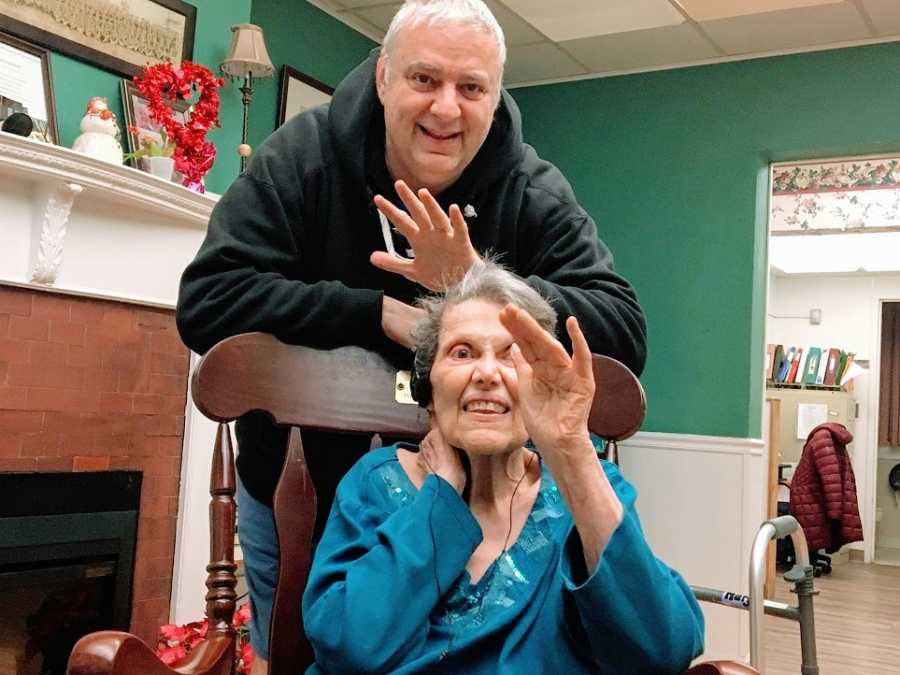 A man stands with an older woman who waves to the camera