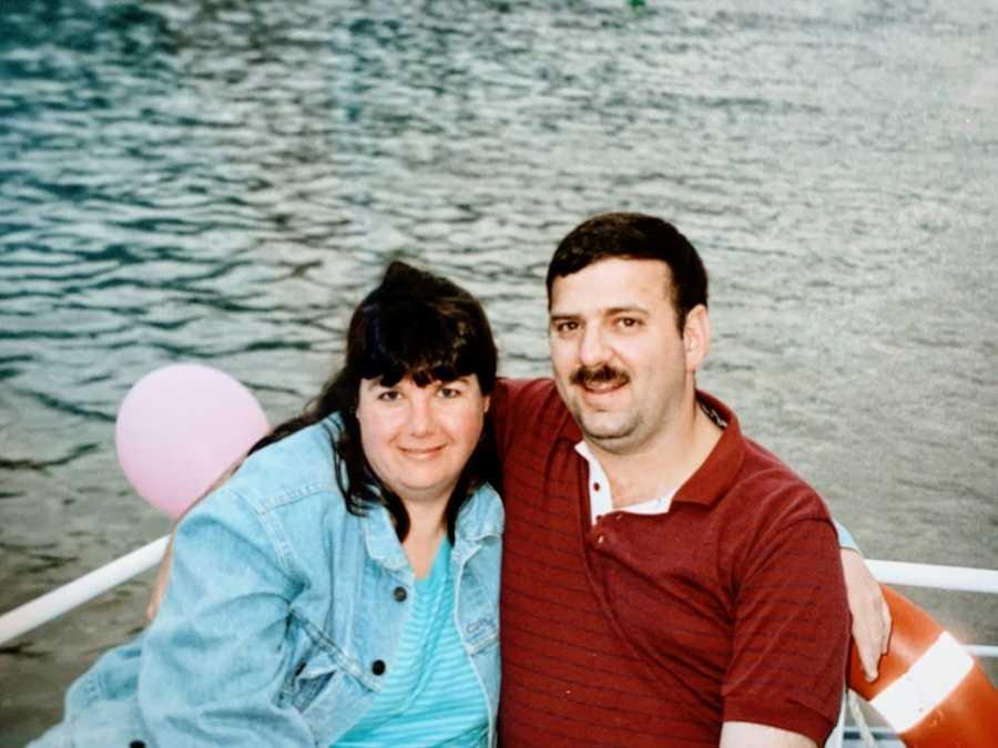 A man and his wife sit together in a small boat