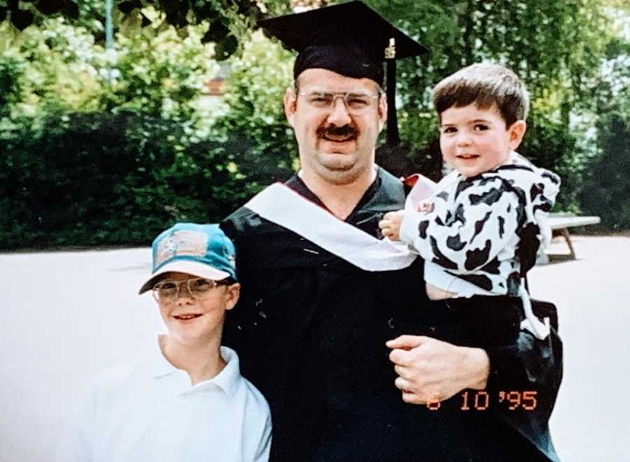 A man in a cap and gown stands with his two young sons