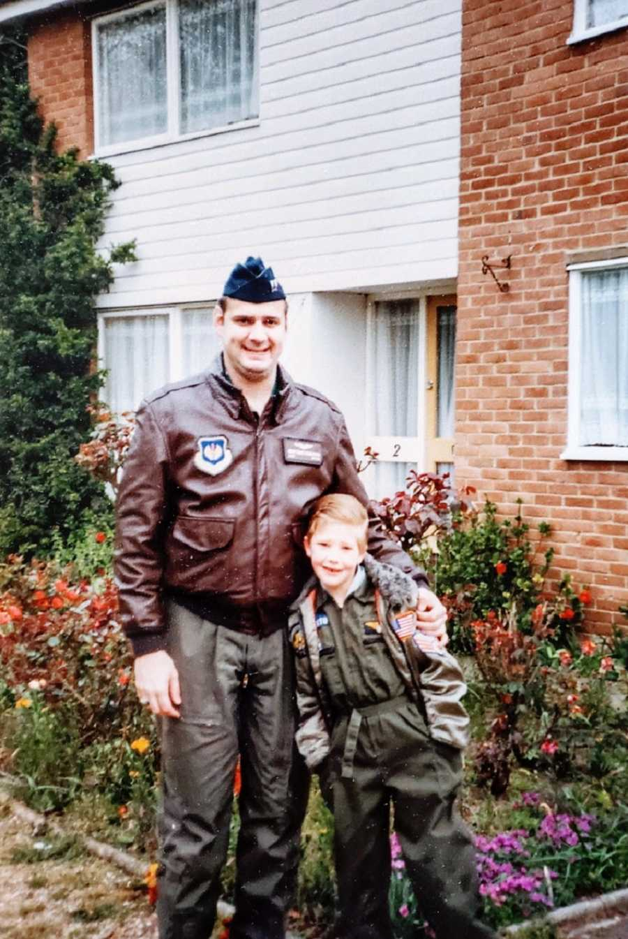 A man in a military uniform stands with a young boy outside