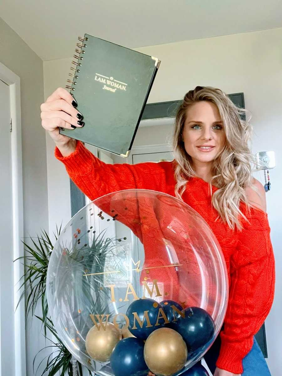 A woman in a red shirt holds up a black journal