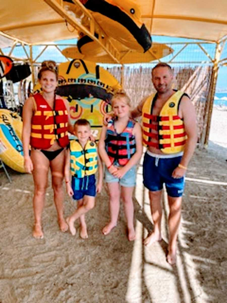 Parents and their two kids wear life vests on a beach
