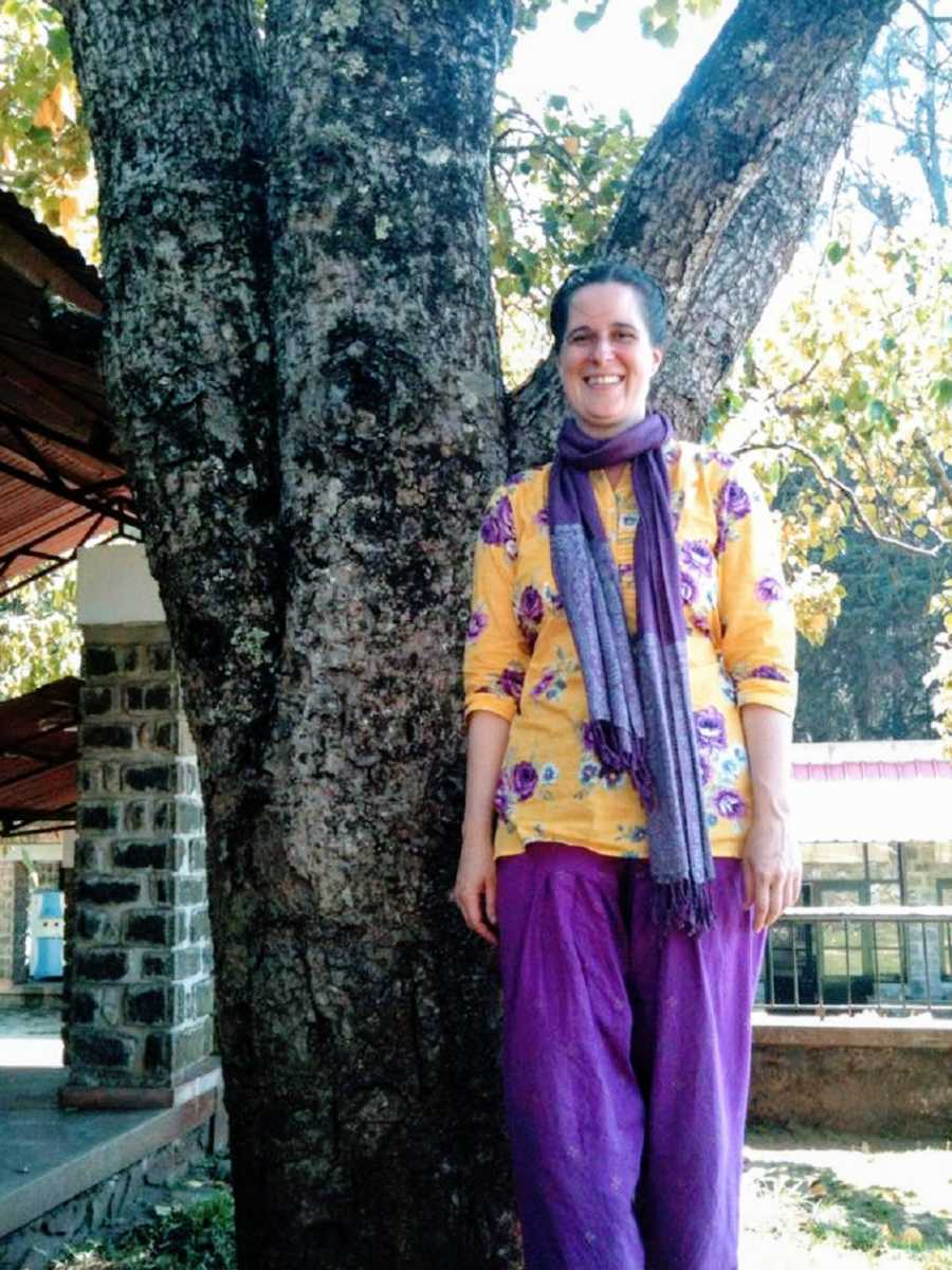 A woman wearing purple and yellow stands by a tree