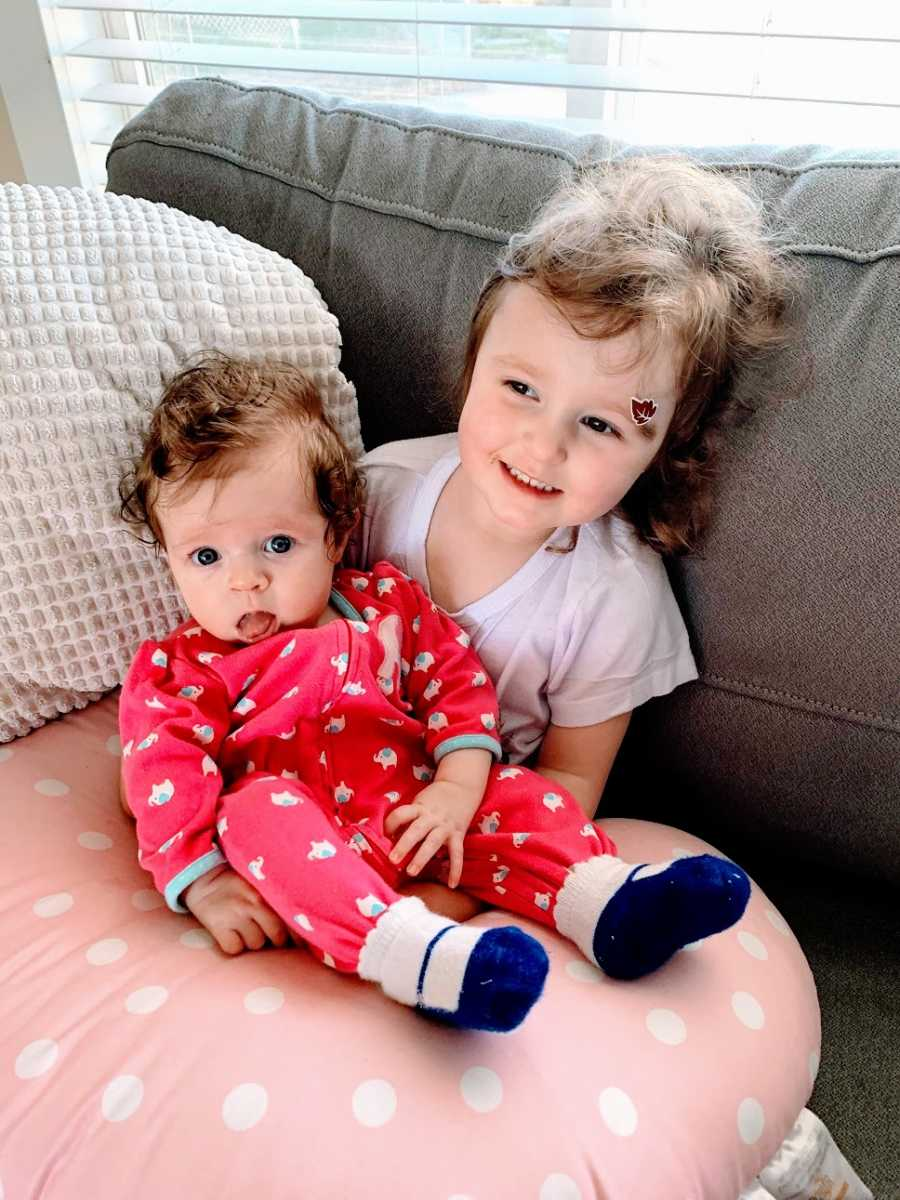 A little girl holds her baby sister