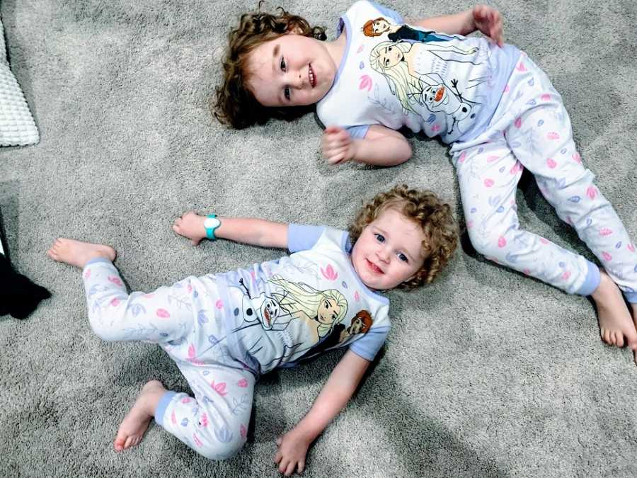 A pair of sisters lie on the floor together