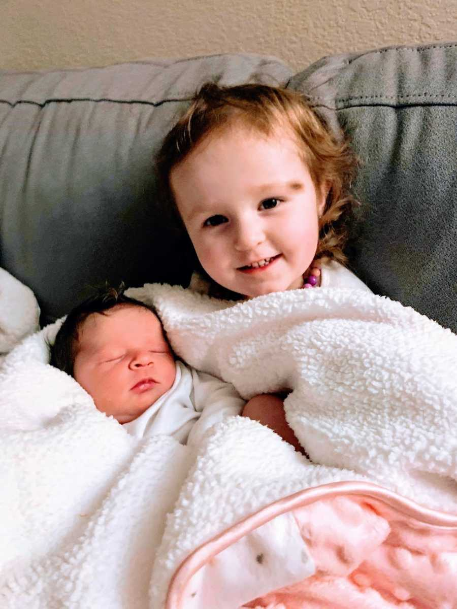 A little girl and her baby sister sit wrapped in blankets