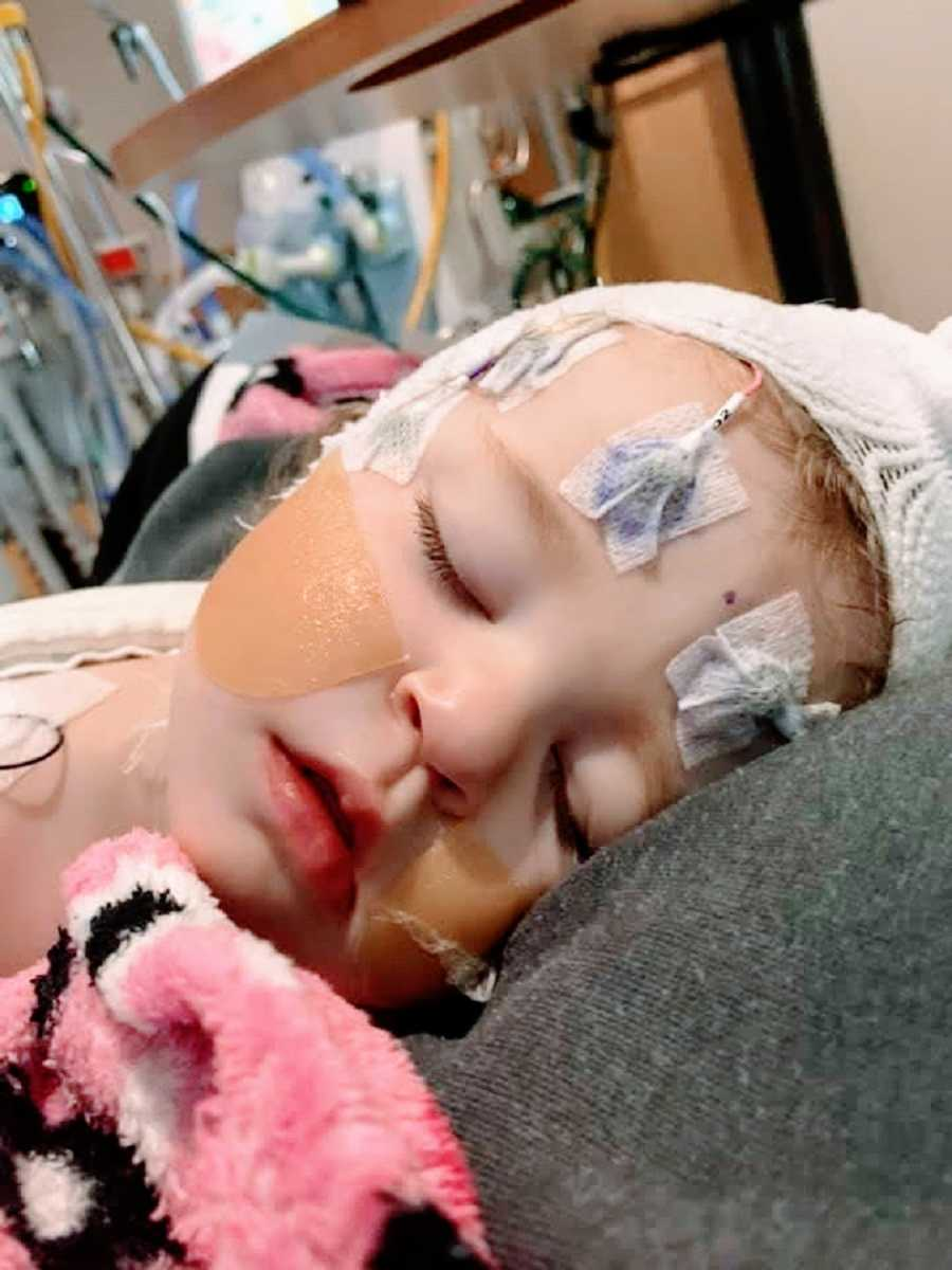 A young girl lies in a hospital bed