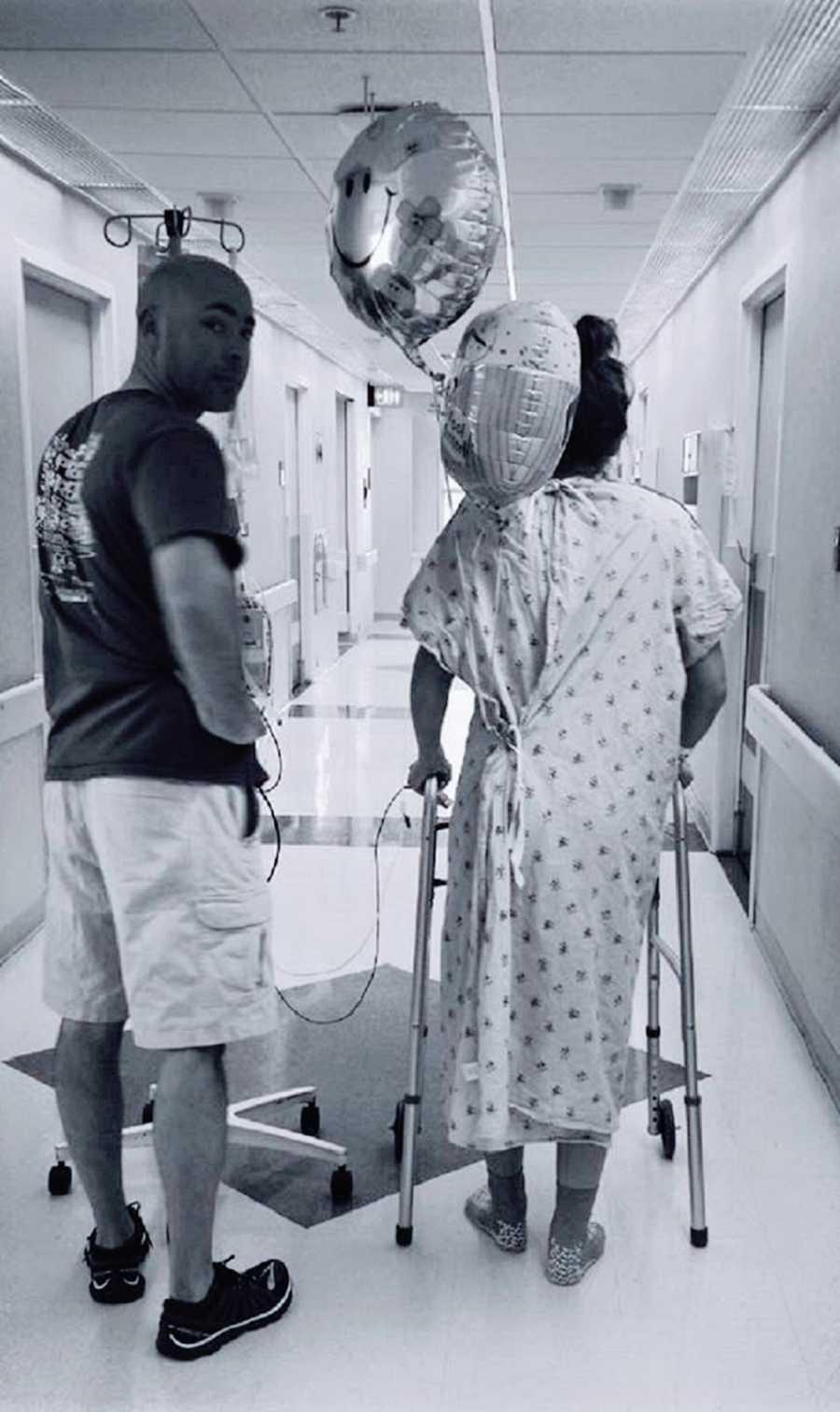 A man and a woman walk down a hospital corridor