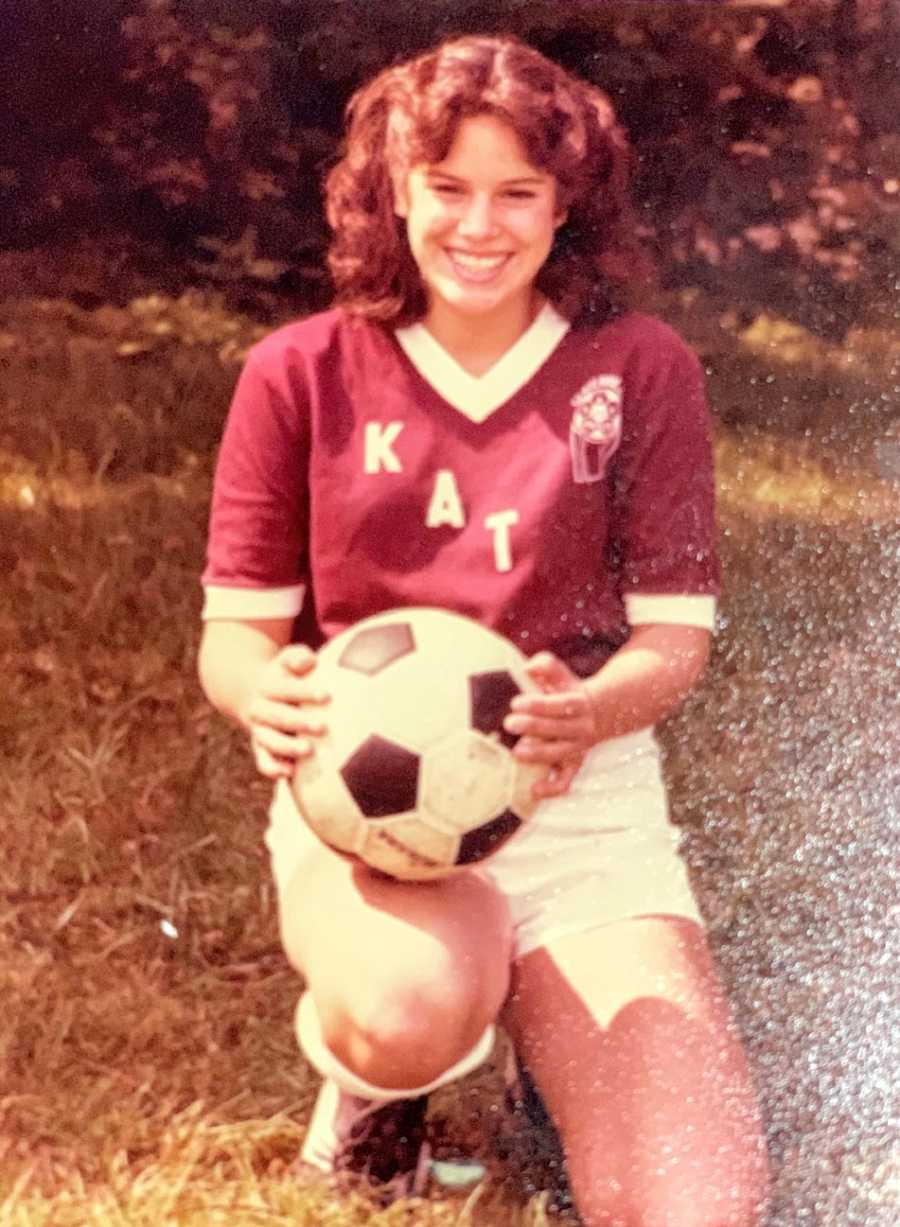 A young woman holds a soccer ball