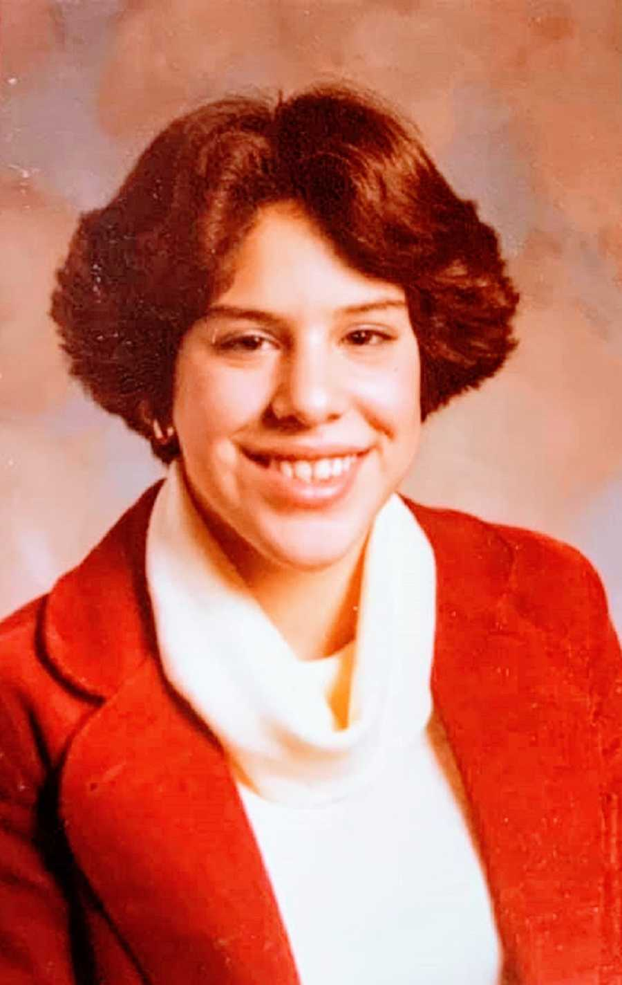 A young woman wearing a red jacket and a turtleneck