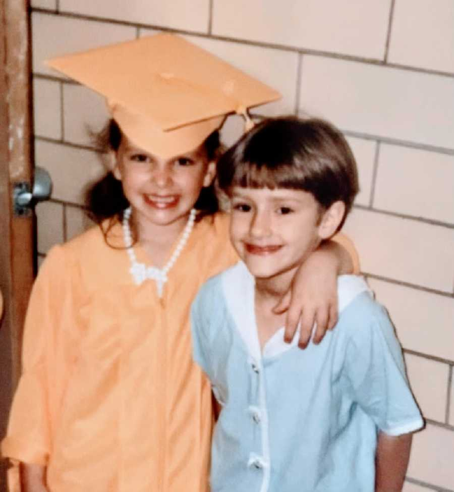 Sisters stand together, one wearing a cap and gown