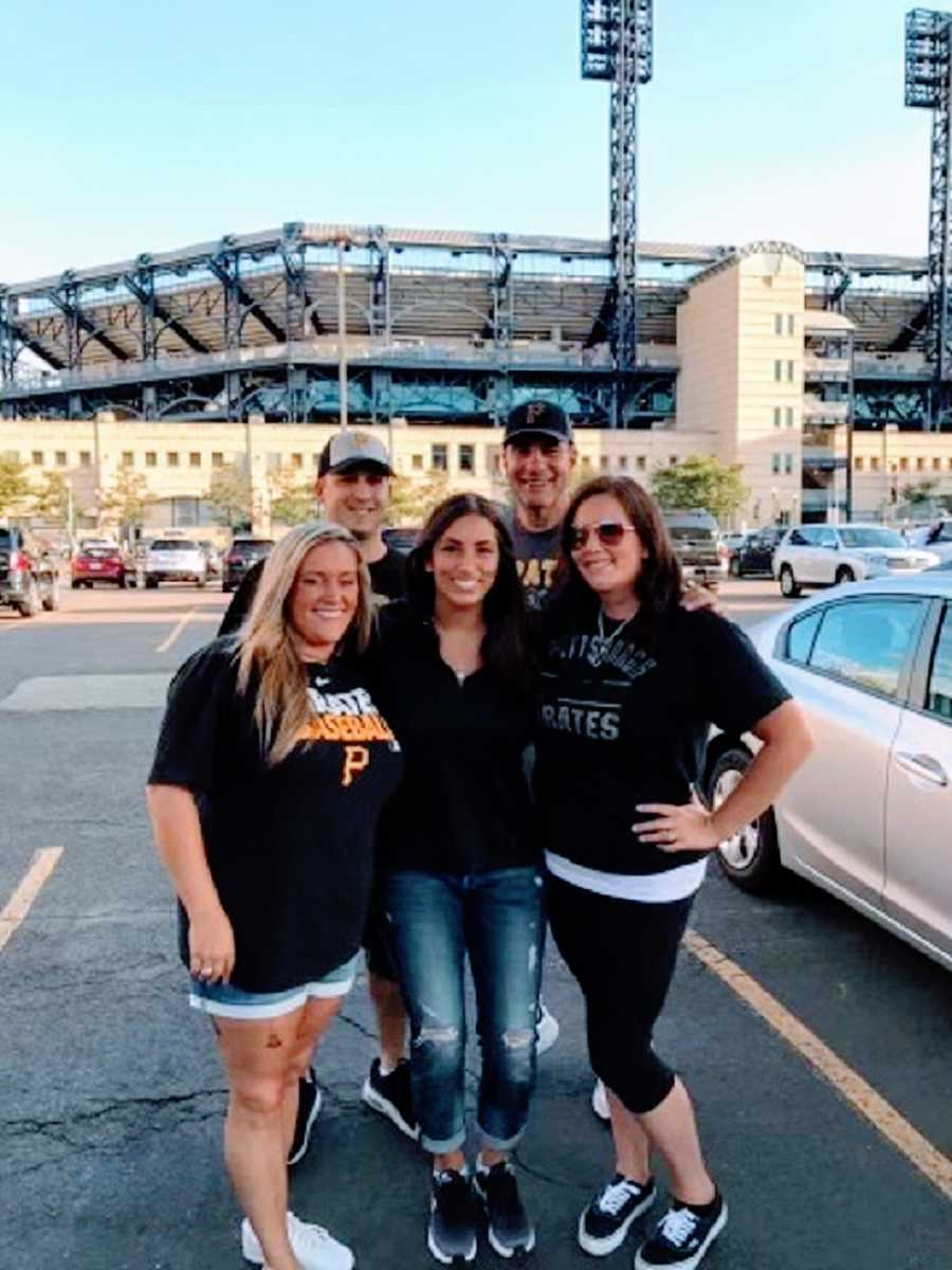 A family stand together outside a baseball stadium