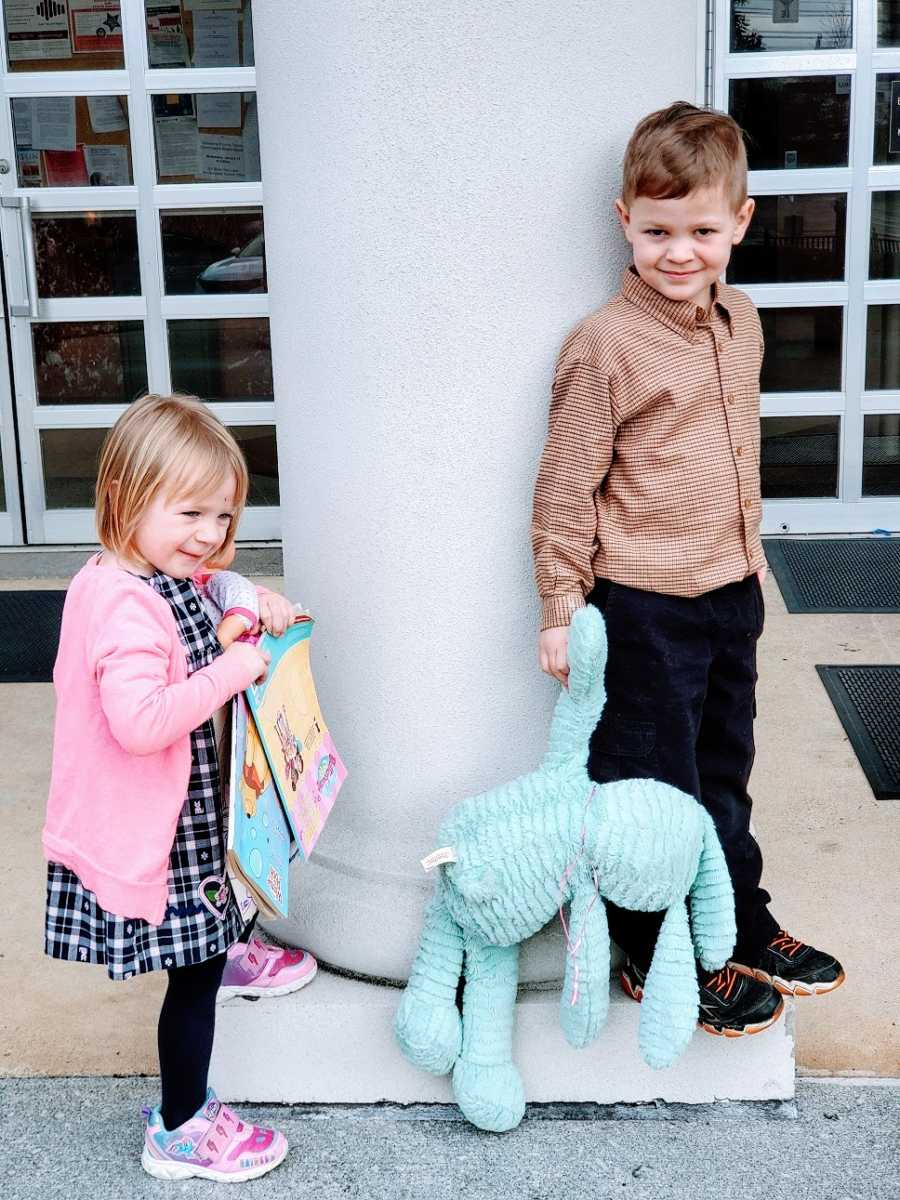 Siblings stand outside a building holding toys