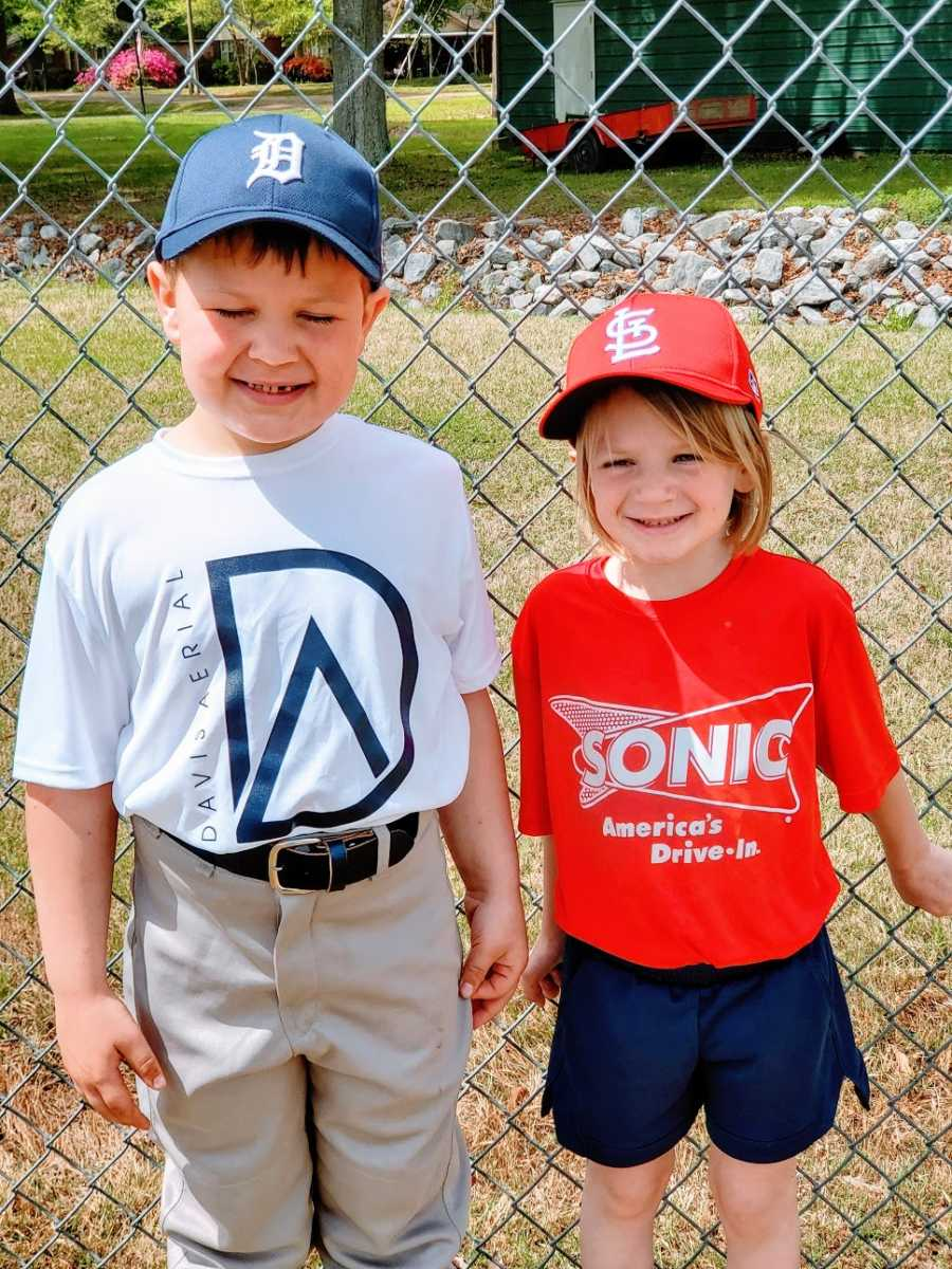 Siblings stand by a fence wearing baseball uniforms