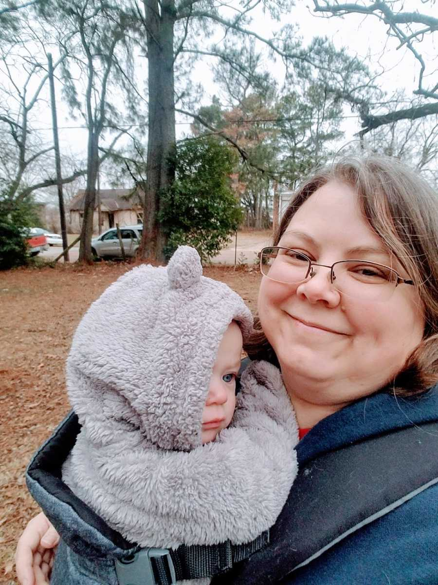 A mother holds her baby girl wearing a coat