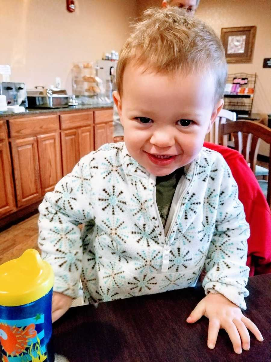 A little boy wearing a shirt with snowflakes on it