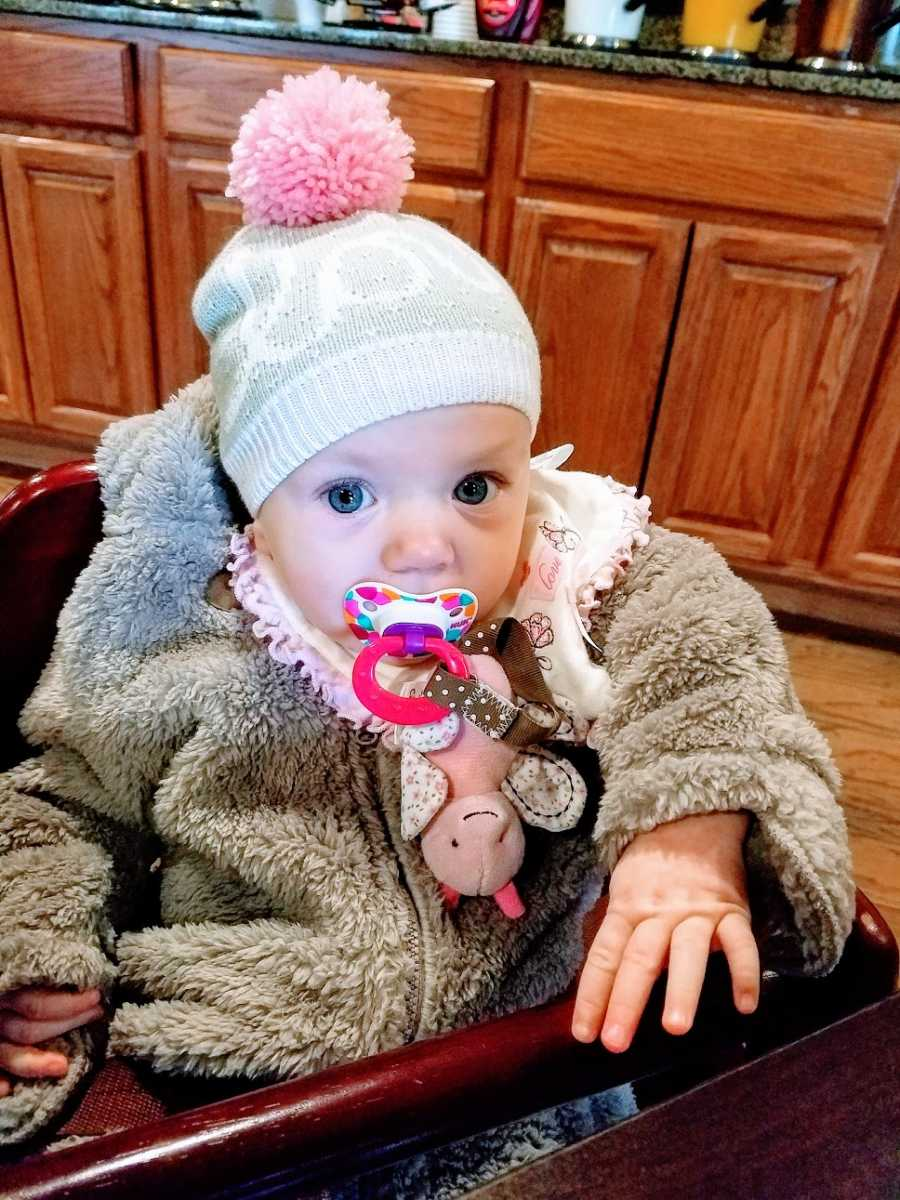 A baby girl with a pacifier wearing a winter coat and hat