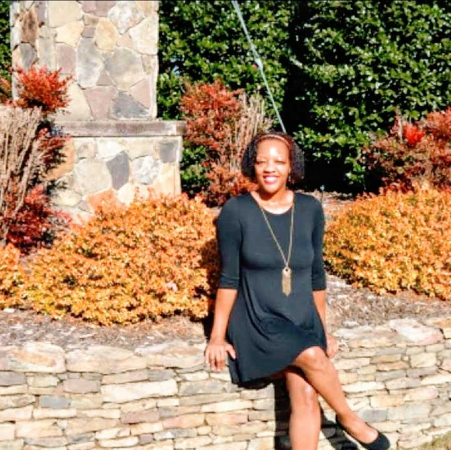A woman sits on a stone wall in a black dress