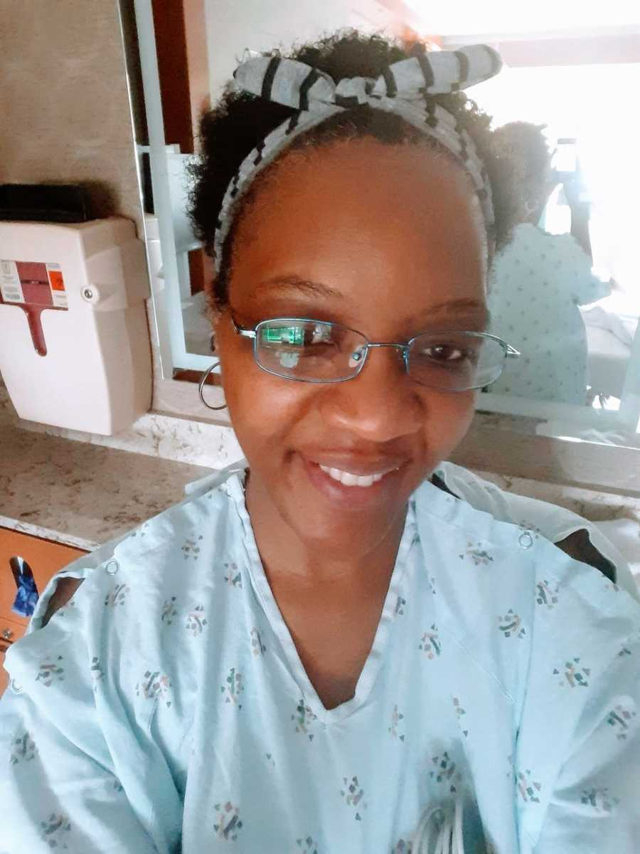 A woman smiling while wearing a hospital gown