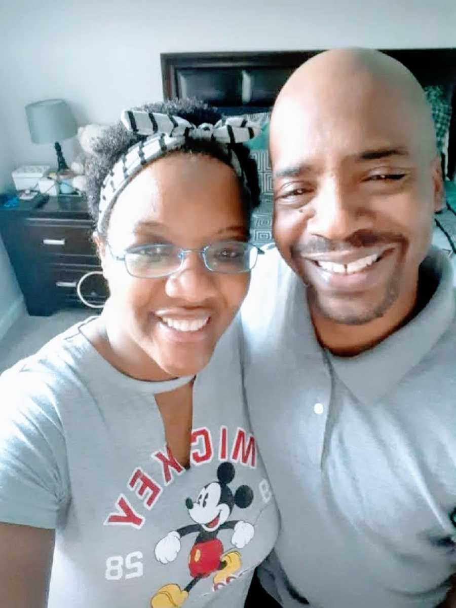 A woman and her husband stand in their bedroom