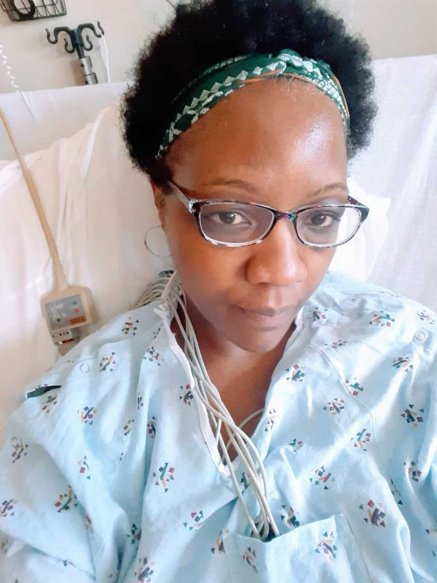 A woman sits in a hospital bed hooked up to wires