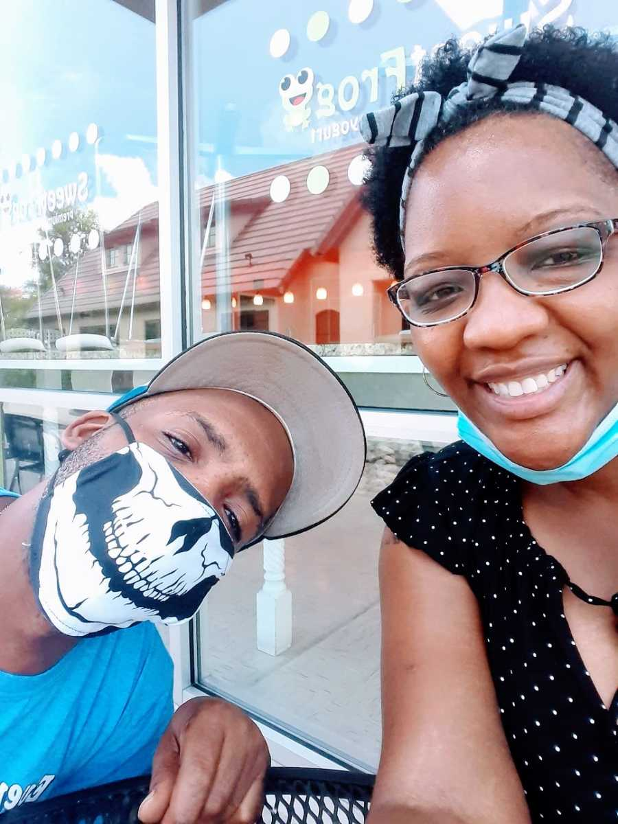 A woman and her husband wear masks at a restaurant