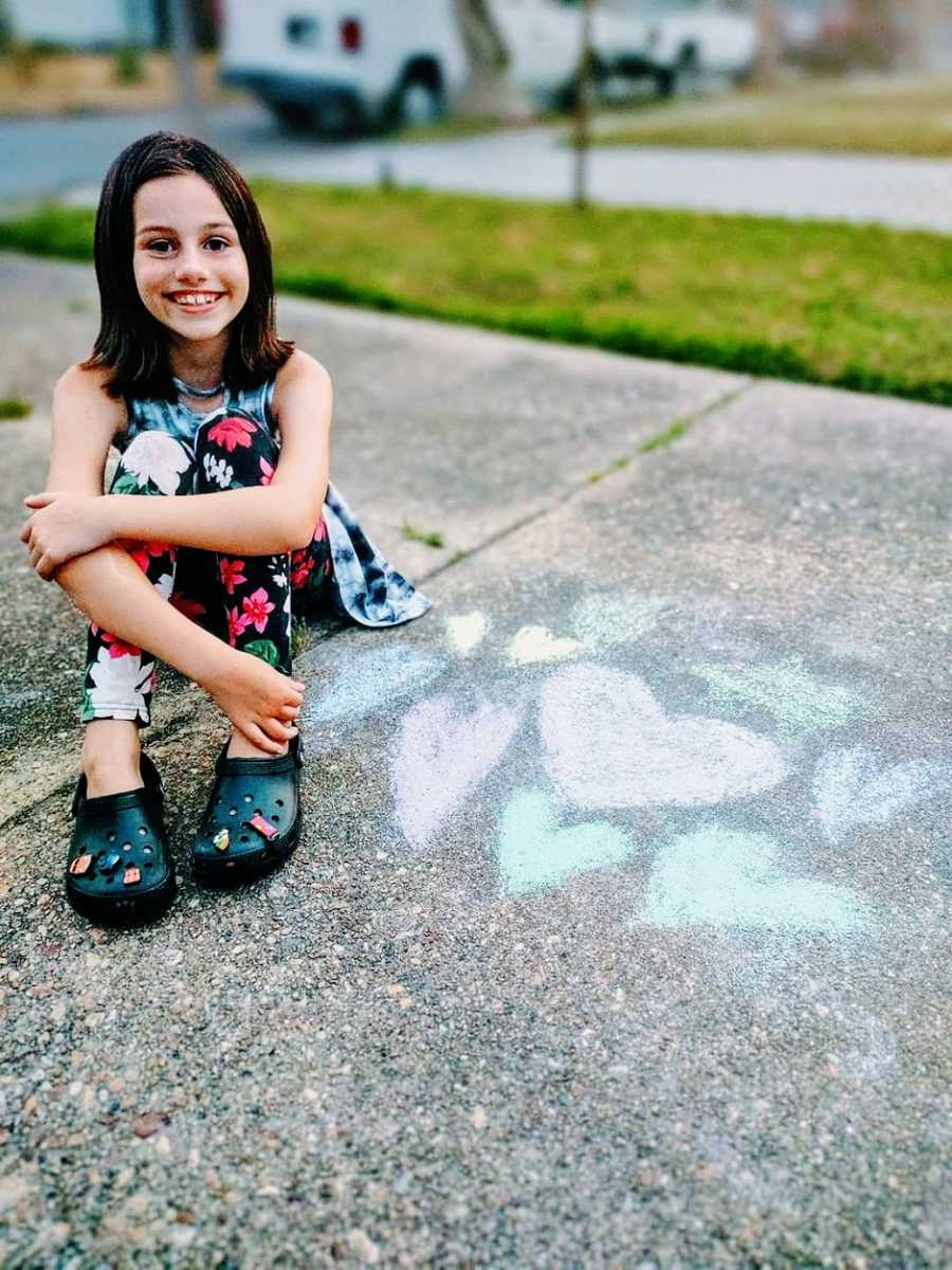 A little girl wearing crocs sits on a sidewalk next to chalk hearts