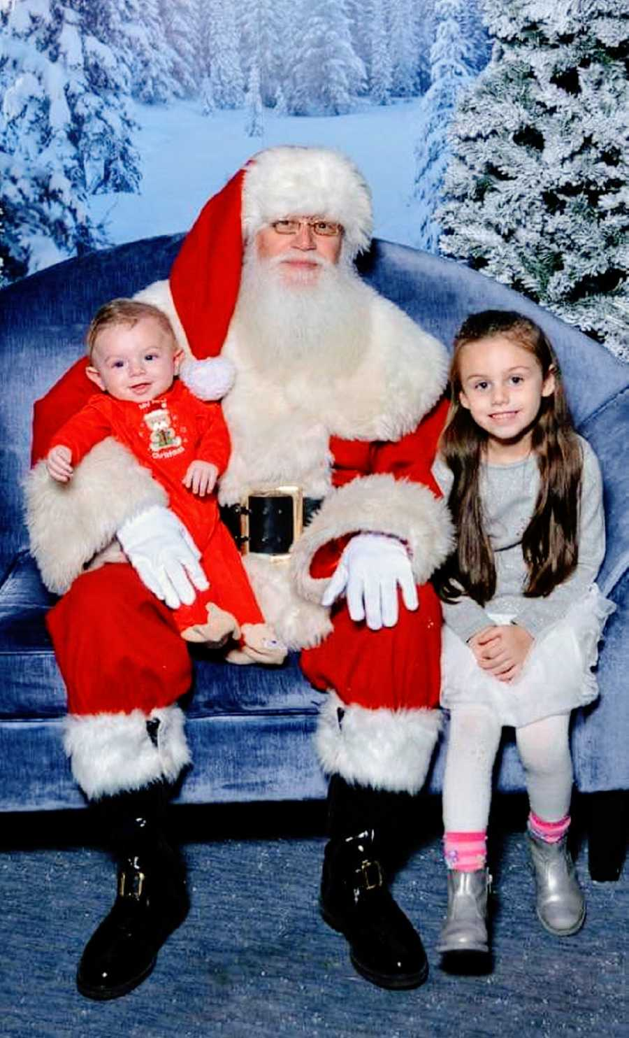 A pair of young children sit with Santa Claus