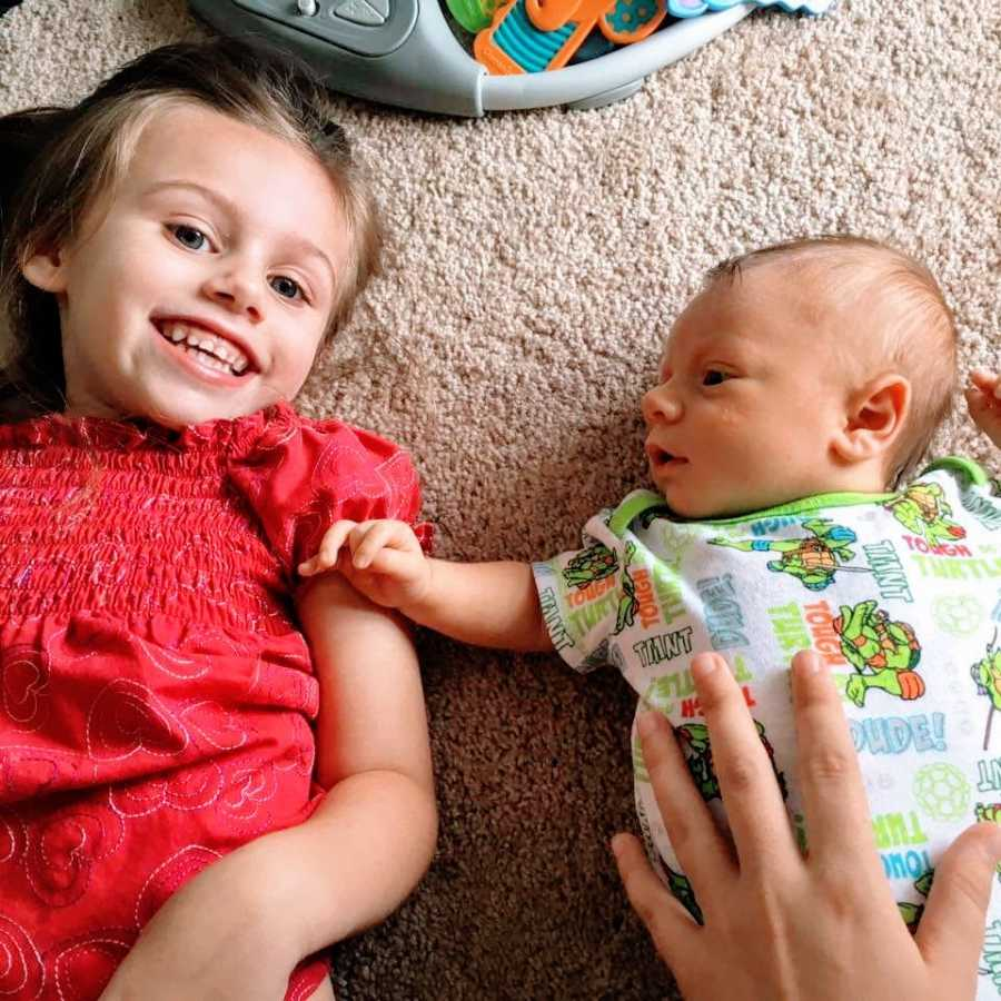 A little girl lies on the floor with her baby brother