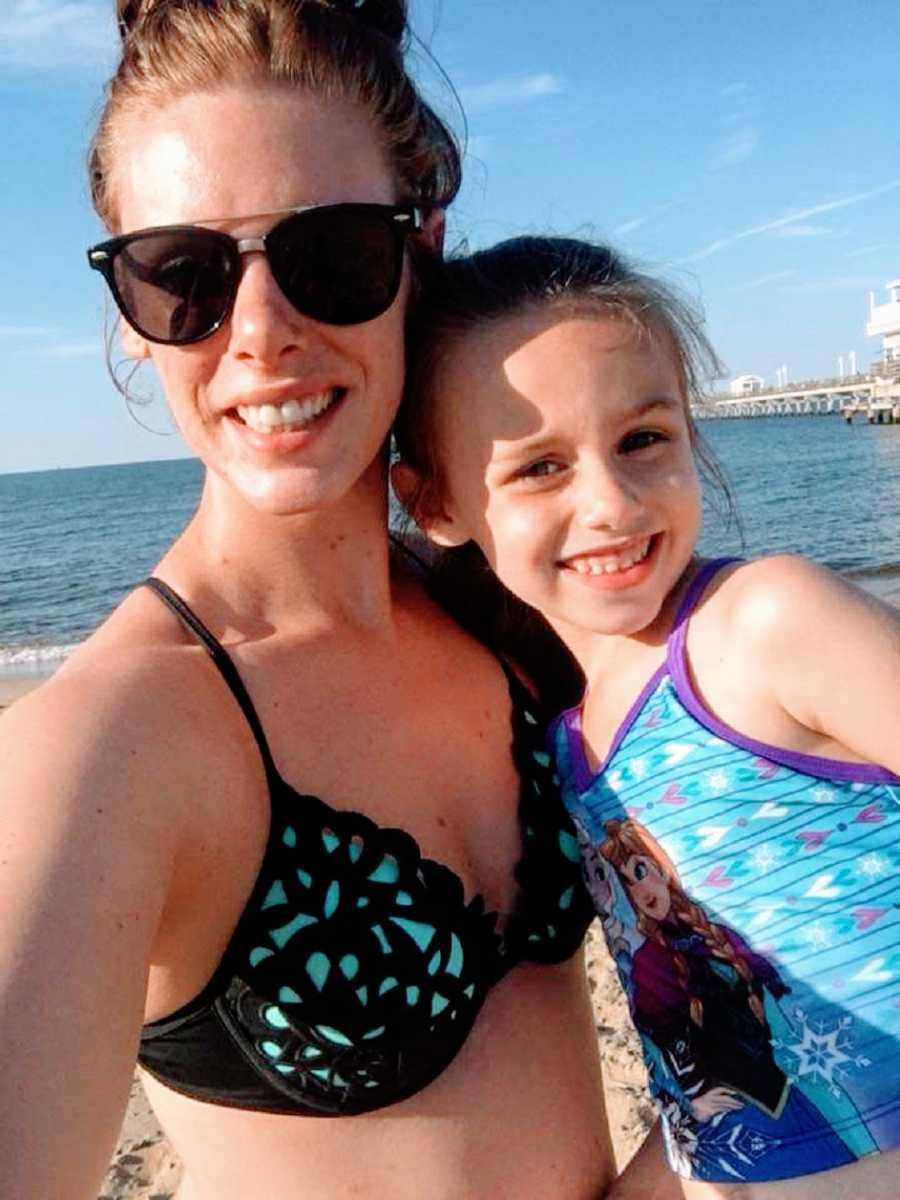 A girl and her mother wearing swimsuits at the beach