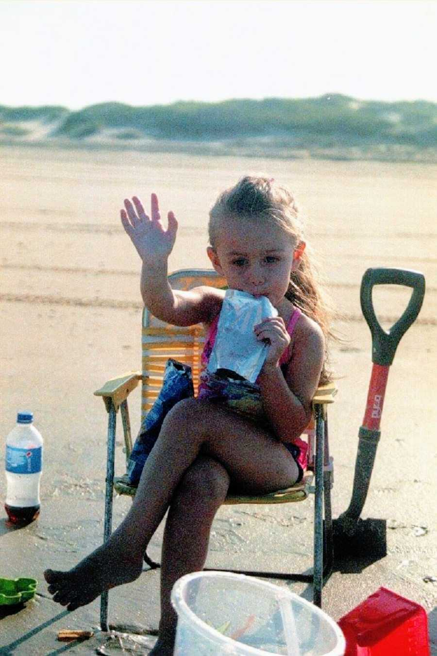 A little girl sits in a lawn chair sipping a juice pouch