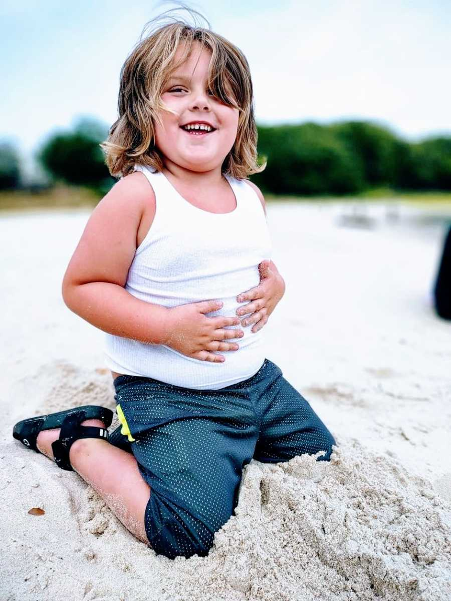 A little boy with autism plays in the sand