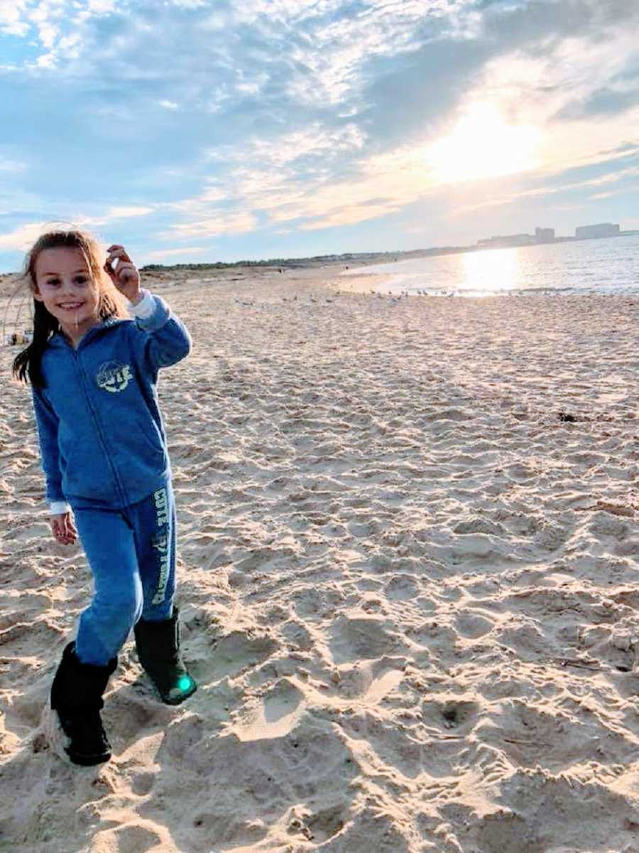 A little girl stands by herself on a beach wearing blue
