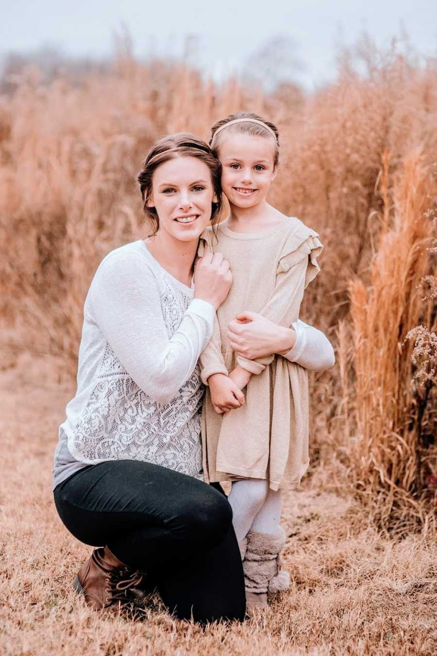 A mom and her daughter stand together in a field