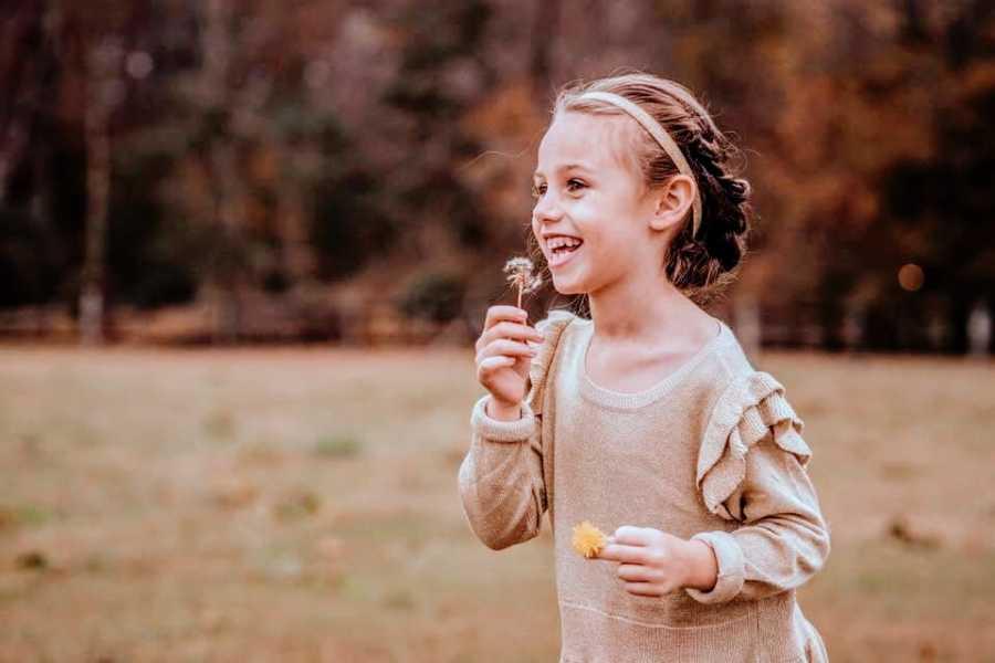 A little girl blows on a dandelion in a field