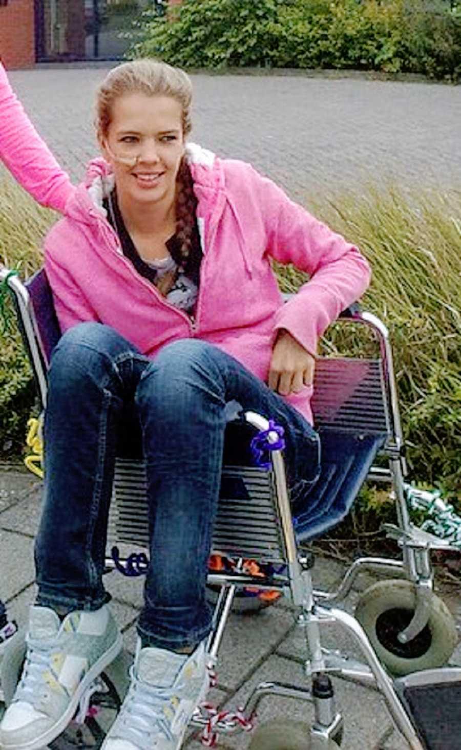 A person sits sideways in a wheelchair
