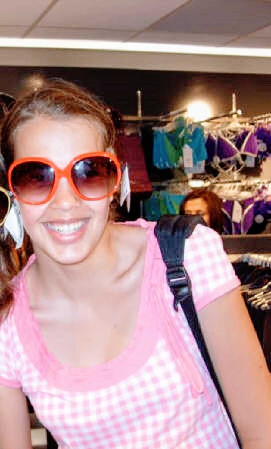 A person wearing a pink shirt and sunglasses