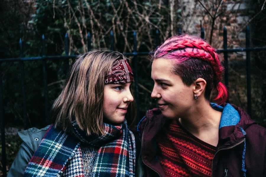 A person with pink hair and their partner