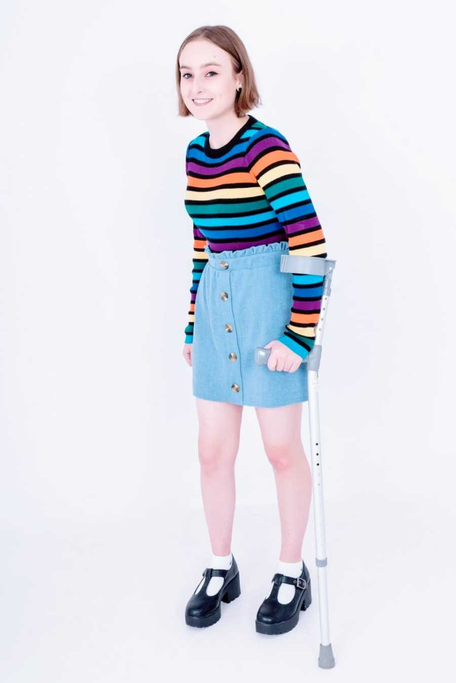 A young woman wearing a rainbow striped shirt stands with the help of a walking stick