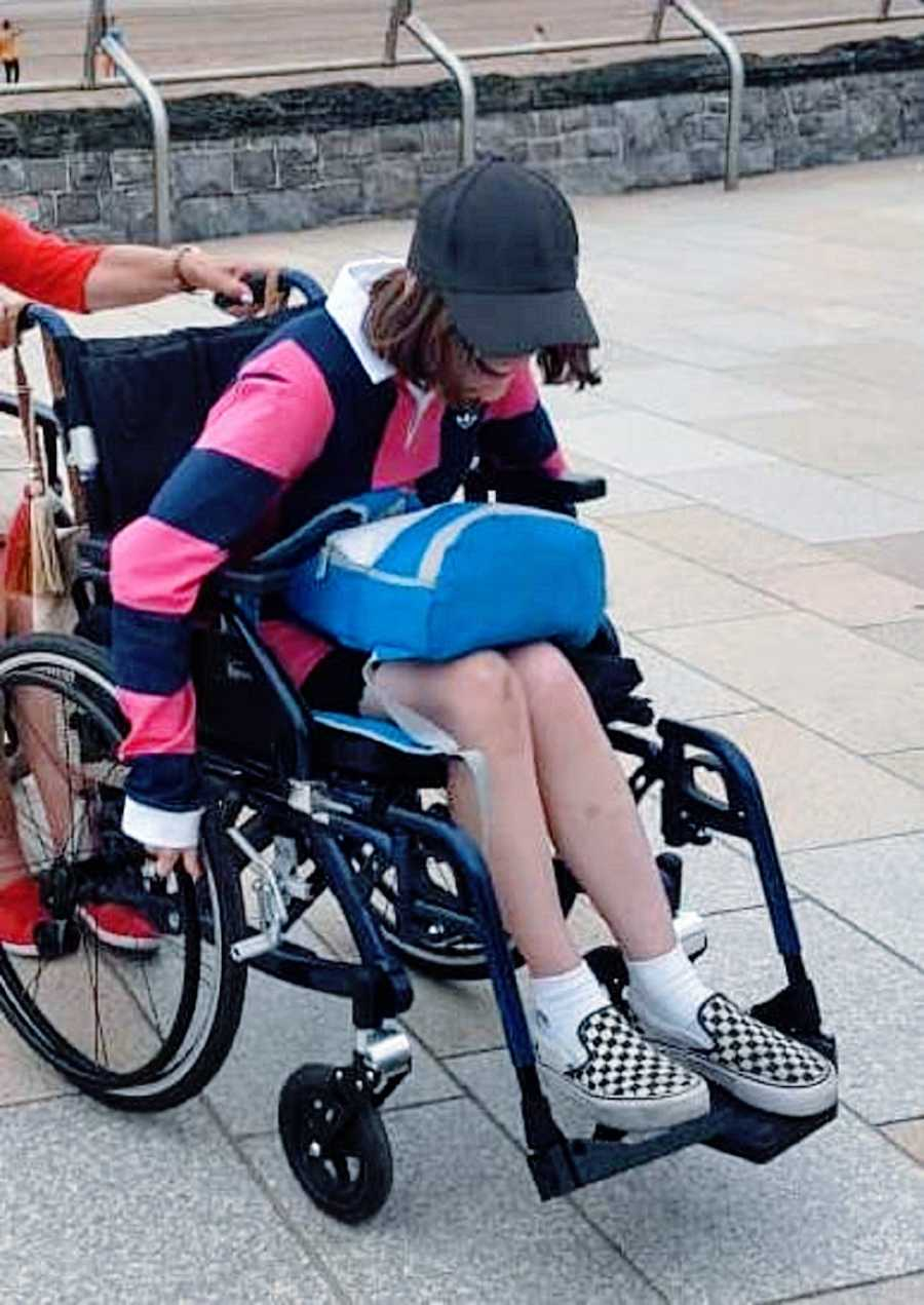 A woman in a wheelchair with a blue backpack on her lap