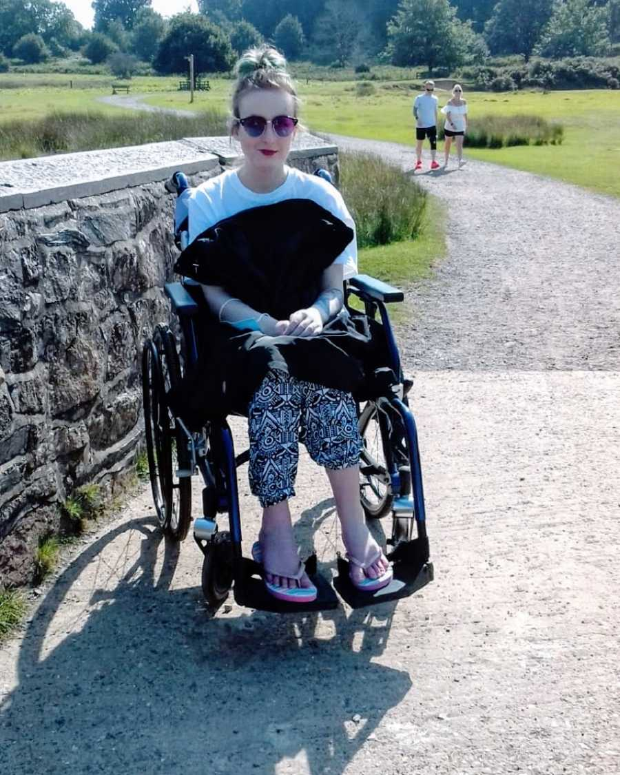 A woman sits in a wheelchair next to a stone wall wearing flipflops and sunglasses
