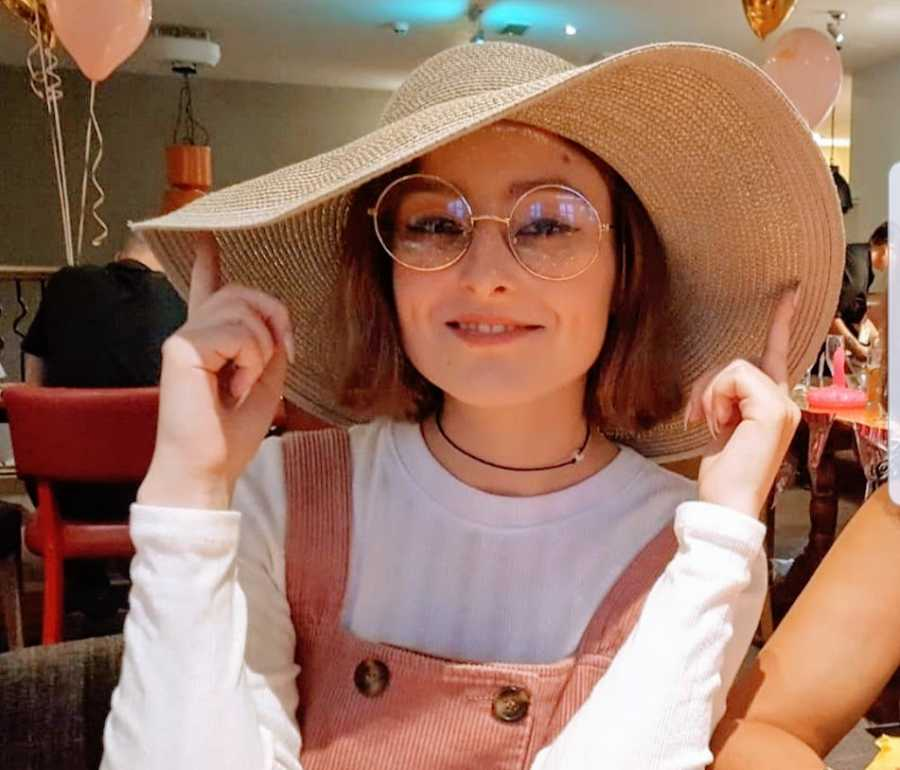 A woman wearing overalls and a large sunhat sits at a table