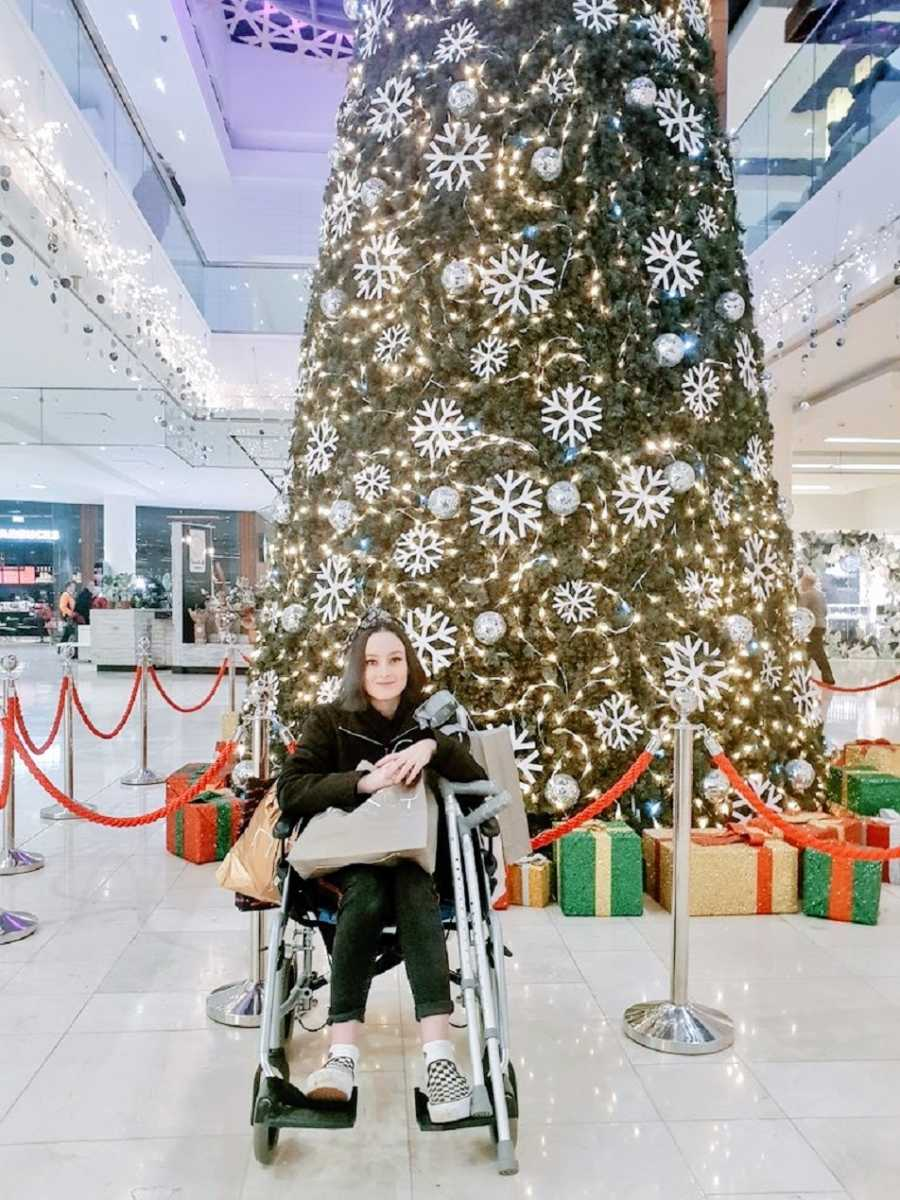 A woman in a wheelchair holds shopping bags near a large Christmas tree