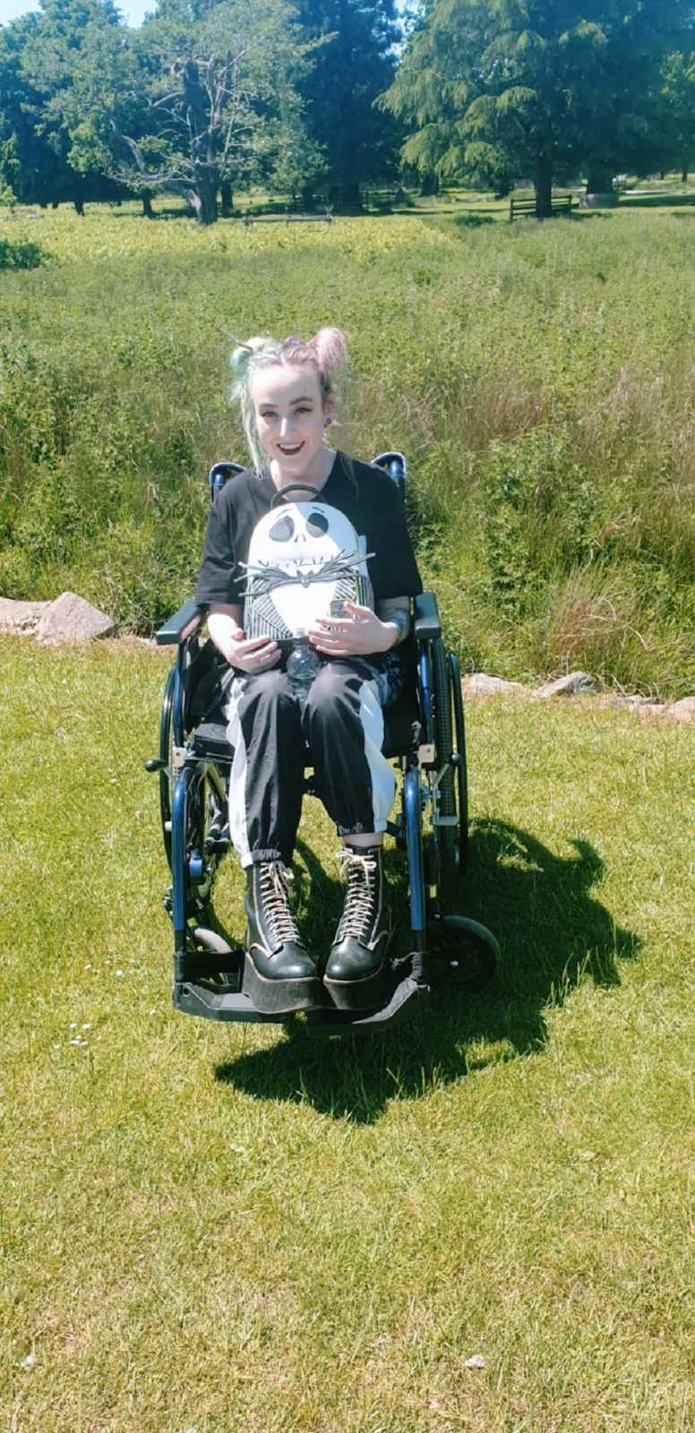 A woman in a wheelchair sits in a field holding a backpack